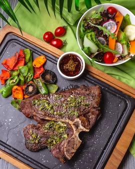 야채 샐러드와 함께 보드에 구운 야채와 소스와 함께 상위 뷰 뼈 스테이크