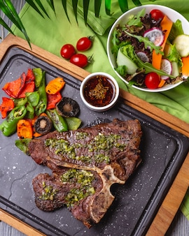 Top view bone steak with grilled vegetables and sauce on the board with vegetable salad