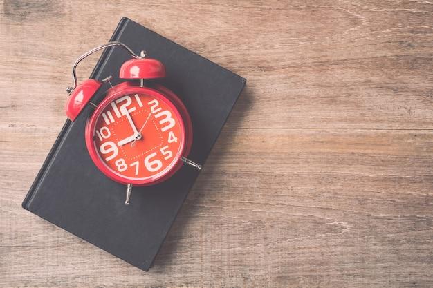 나무 판자 배경에 상위 뷰 책 및 빨간 시계. 개념을 읽는 시간