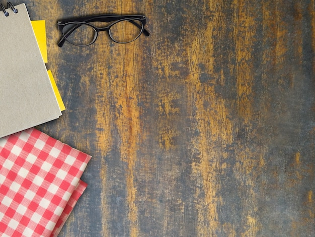 Top view of book and eyeglasses and plaid on wooden of brown, mock up
