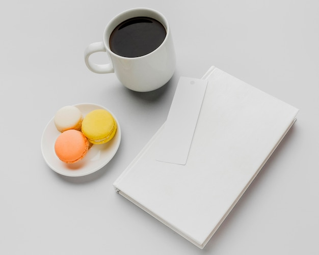 Top view book with coffee and macarons