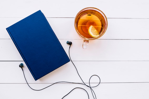 Top view book with tea and earphones