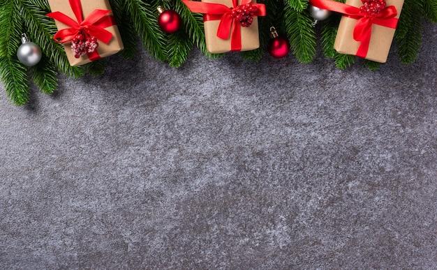 Вид сверху границы зеленые сосновые шишки еловые ветки с рождественским украшением и подарочной коробкой