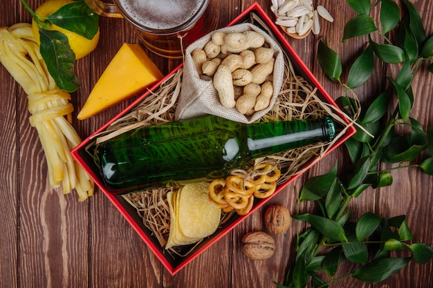 Top view of bottle of beer with peanuts in a sack potato chips and mini pretzels on straw in a red box and a mug of beer with cheese and lemon on rustic