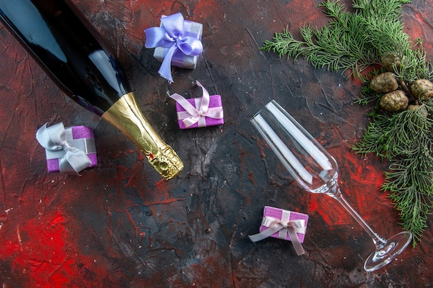 Top view bottle of champagne with little presents on dark color drink alcohol photo new year party