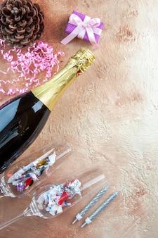 Bottiglia di champagne vista dall'alto con piccoli regali su alcol a colori per foto di natale regalo leggero
