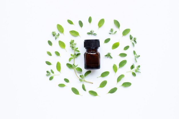 Top view. bottle of essential oil with marjoram on white