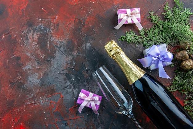 暗い色の飲み物のアルコール写真の新年会に少しプレゼントを添えたシャンパンのトップビューのボトル