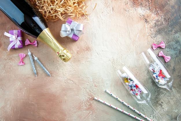 光の新年の色のギフト アルコール フォト パーティーに小さなプレゼントとシャンパンのトップ ビュー ボトル