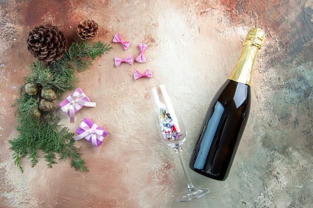 光のギフト クリスマス写真新年色アルコールに小さなプレゼントとシャンパンのトップ ビュー ボトル