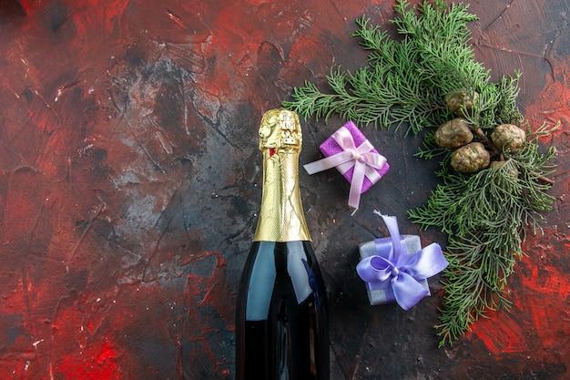 暗い色の飲み物のアルコール写真の新年会にプレゼントを添えたシャンパンのトップビューボトル