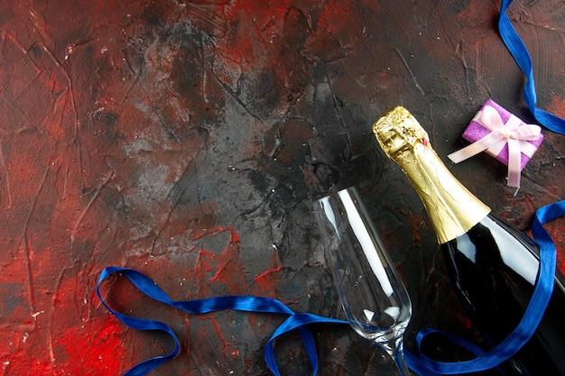 暗い飲み物のアルコール写真の色にワイングラスを使ったシャンパンのトップビューボトル