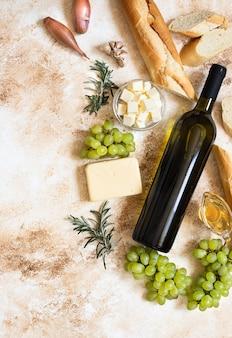 Бутылка белого вина, виноград, сыр, масло и багет вид сверху