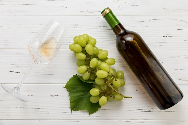 Top view bottle of wine with glass and bunch of grapes