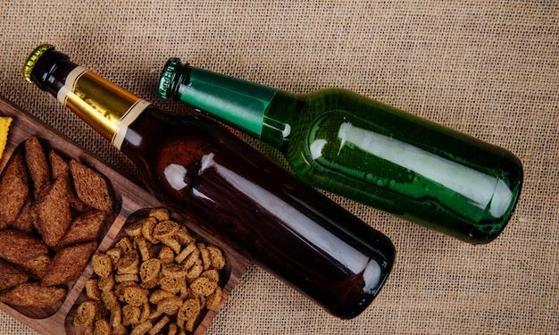 Top view of  bottles of bee with bread crackers on sackcloth texture