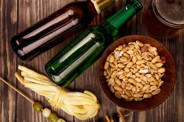 Vista dall'alto di bottiglie di birra con arachidi in una ciotola e olive in salamoia con formaggio a pasta filata su rustico