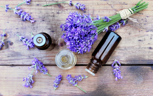 Top view on bottles of essential oil and bouquet of  lavender flower arranged on a wooden table