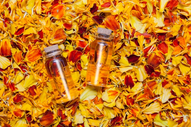 Top view bottles of oil or tincture against a surface of bright orange petals