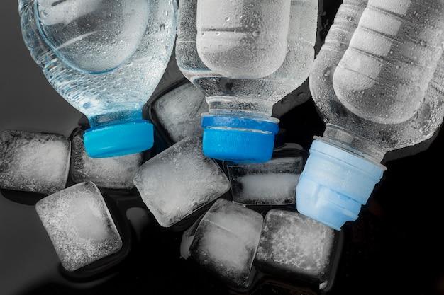 Vista dall'alto bottiglie d'acqua e cubetti di ghiaccio