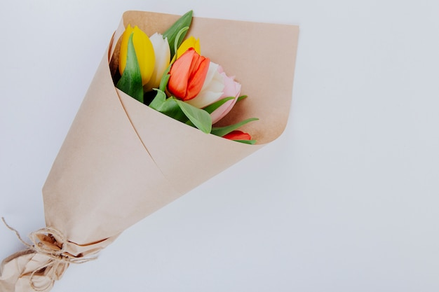 Top view of a bouquet of colorful tulip flowers in a craft paper on white background with copy space