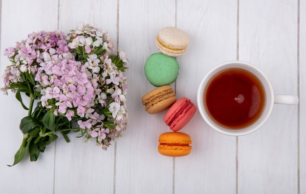 Top view of bouquet of flowers with a cup of tea and colored macarons on a white surface