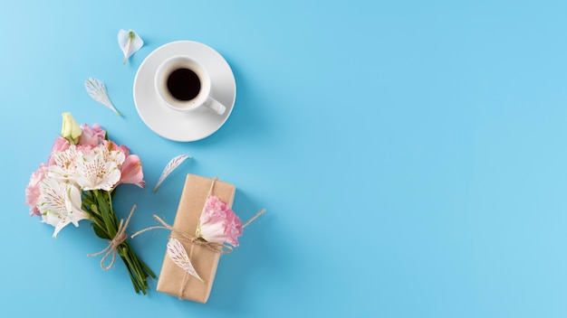 Vista dall'alto del mazzo di fiori con confezione regalo e tazza di caffè