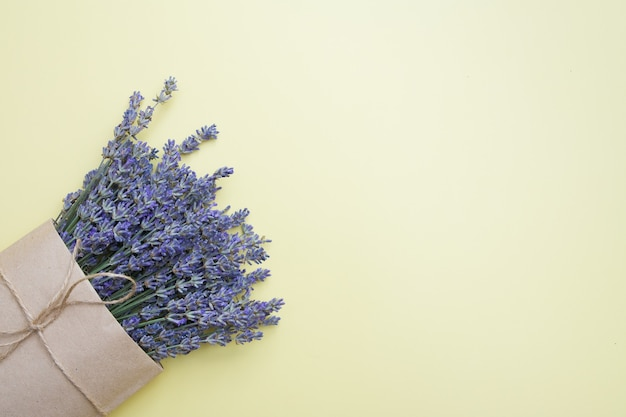 Top view of a bouquet of lavender in a craft bag on a yellow surface