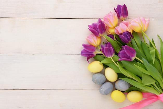 コピースペースと白い木製の背景にピンクと紫のチューリップとイースターパステル黄色と青の卵の上面花束