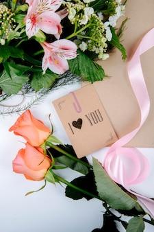 Vista dall'alto di un bouquet di fiori di colore rosa alstroemeria con fioritura viburno e una cartolina con rose color corallo su sfondo bianco