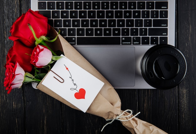 Top view a bouquet of red roses in craft paper with attached postcard lying on a laptop with a paper cup of coffee on dark wooden background