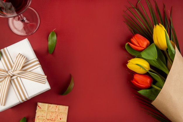 Top view of a bouquet of red and yellow color tulips with a glass of wine, white chocolate and a gift box on red table with copy space