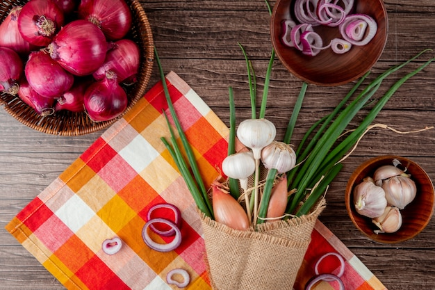 Top view of bouquet of vegetables as green onion garlic shallot on plaid cloth on wooden background