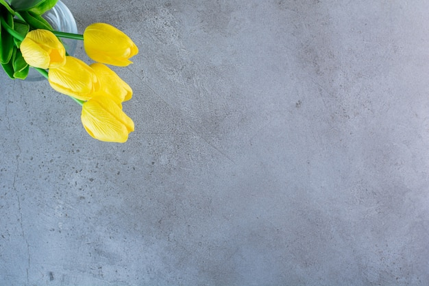 Top view of a bouquet of yellow tulips in a glass vase on the gray background.
