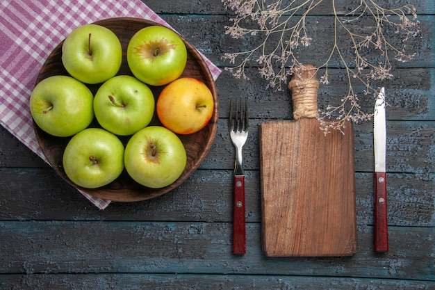 Top view bowl of apples bowl of seven green-yellow apples on checkered tablecloth next to branches fork knife and cutting board