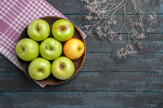 Top view bowl of apples bowl of seven green-yellow apples on checkered tablecloth next to branches