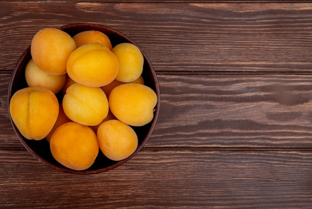 Top view of bowl of apricots on wooden background with copy space
