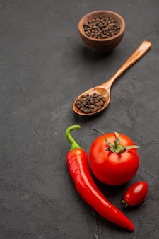 Vista dall'alto una ciotola di pepe nero e pomodoro peperoncino rosso e un pomodoro ciliegino su sfondo nero