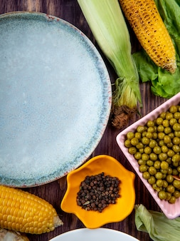 Top view of bowl of black pepper with empty plate corns green peas on wooden surface