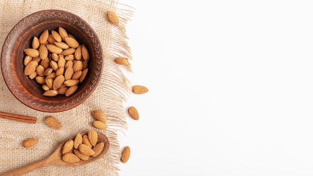 Top view of bowl on burlap with almonds and copy space