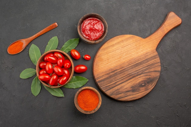 Top view a bowl of cherry tomatoes bay leaves a chopping board a wooden spoon and bowls of ketchup and hot pepper powder on the black table
