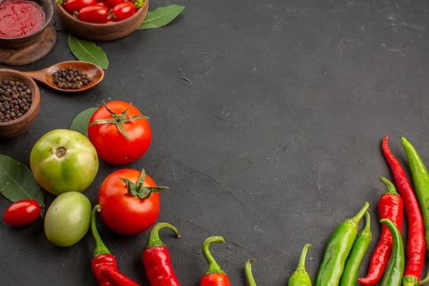 Vista dall'alto una ciotola di pomodorini peperoni rossi e verdi caldi e pomodori foglie di alloro ciotole di ketchup pepe nero e un cucchiaio su fondo nero