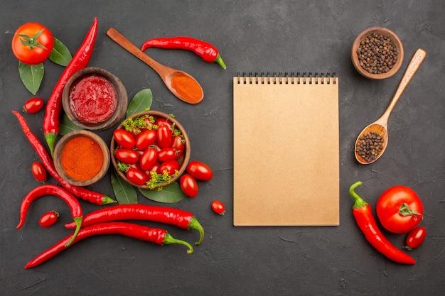 Vista dall'alto una ciotola di pomodorini peperoni rossi piccanti pepe nero in un cucchiaio di legno foglie di alloro ciotole di ketchup e polvere di peperoncino un taccuino su fondo nero