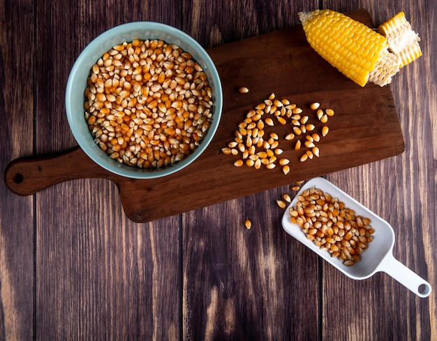 Top view of bowl of corn seeds cut corn on cutting board with spoon full of corn seeds on wood