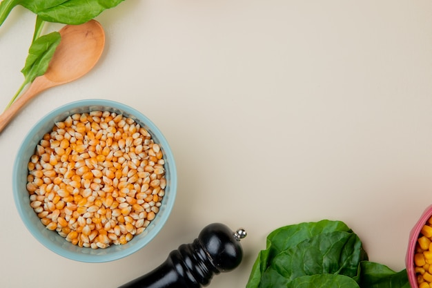 Top view of bowl of corn seeds with spinach and wooden spoon on white surface with copy space