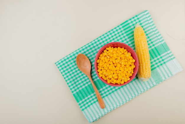 Top view of bowl of corn seeds with spoon and corn on cloth and white with copy space