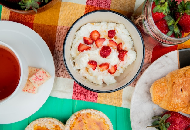Top view of bowl of cottage cheese with strawberries cup of tea crispbreads crescent roll on cloth on green surface