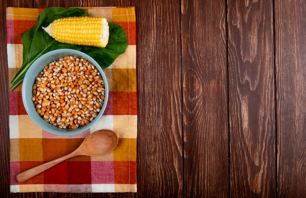 Top view of bowl of dried corn kernel with cooked corn wooden spoon and spinach on cloth and wooden surface with copy space
