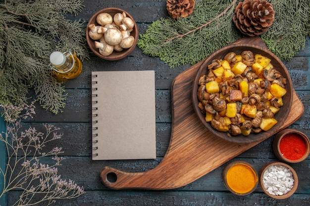 Top view bowl of food plate of mushrooms and potatoes on the cutting board next to the notebook between the bottle of oil bowl of white mushrooms spruce branches and colorful spices