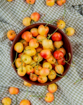 Top view of bowl full of yellow and red cherries on plaid cloth surface