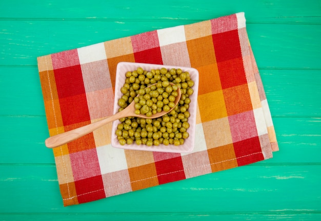 Top view of bowl of green pea with wooden spoon on cloth and green surface